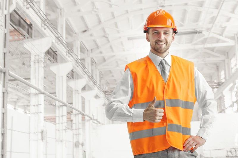 The builder in orange helmet against industrial background
